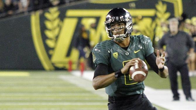 Oregon quarterback Marcus Mariota, right, avoids Arizona defender Sir Thomas Jackson as he looks for a receiver during the second half of their NCAA college football game in Eugene, Ore., Saturday, Sept. 22, 2012.   Mariota threw for 260 yards and two touchdowns as Oregon won 49-0.(AP Photo/Don Ryan)