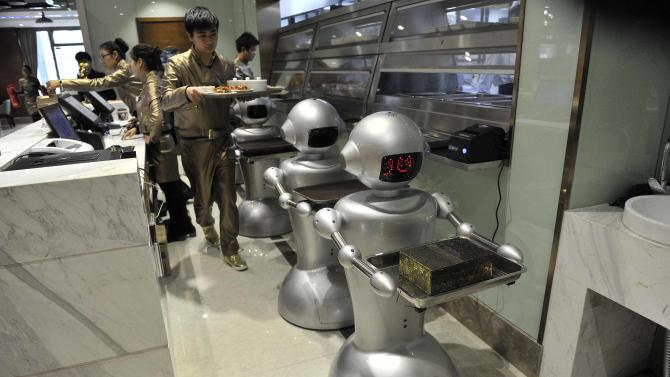 A man puts dishes on robots for delivery at a restaurant in Hefei
