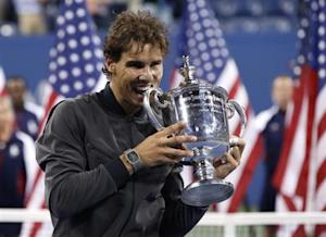 Nadal of Spain bites his trophy after defeating Djokovic of Serbia in their men's final match at the U.S. Open tennis championships in New York