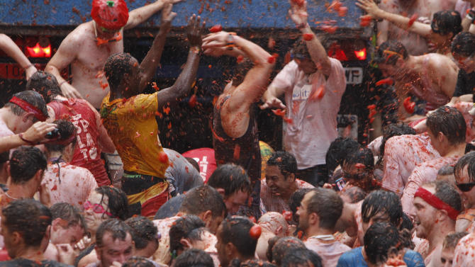 """Crowds of people throw tomatoes at each other during the annual """"tomatina"""" tomato fight fiesta in the village of Bunol, 50 kilometers outside Valencia, Spain, Wednesday, Aug. 28, 2013. Thousands of people are splattering each other with tons of tomatoes in the annual """"Tomatina"""" battle in recession-hit Spain, with the debt-burdened town charging participants entry fees this year for the first time. Bunol town says some 20,000 people are taking part in Wednesday's hour-long street bash, inspired by a food fight among kids back in 1945. Participants were this year charged some 10 euros ($13) to foot the cost of the festival. Residents do not pay. (AP Photo/Alberto Saiz)"""