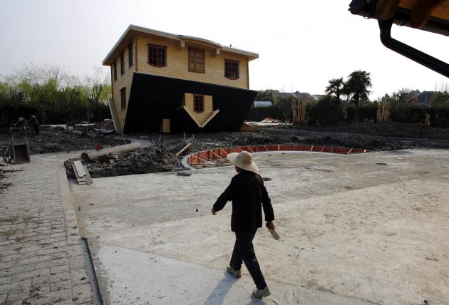 A female labourer walks next to an upside-down house under construction at Fengjing Ancient Town, Jinshan District