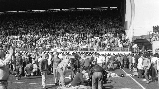 FILE - This is an April 15, 1989 file photo of fans on the pitch receiving attention after severe crushing at Hillsborough stadium in Sheffield England during an FA Cup semi-final football match between Liverpool and Nottingham Forest.  A London court Wednesday Dec. 19, 2012  has overturned a previous ruling that the death of 96 Liverpool fans in the 1989 Hillsborough disaster was accidental, and a new criminal investigation into the stadium tragedy was ordered. The wrongdoing and mistakes that led to the crush at an FA Cup semifinal against Nottingham Forest were only fully exposed in September after an independent panel examined previously secret documents, vindicating a 23-year search for the truth by the victims' families. (AP Photo/PA, File) UNITED KINGDOM OUT