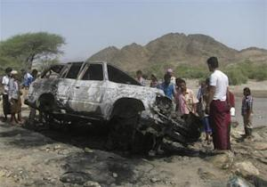 People gather at the site of a drone strike on the road between Yafe and Radfan districts of the southern Yemeni province of Lahj