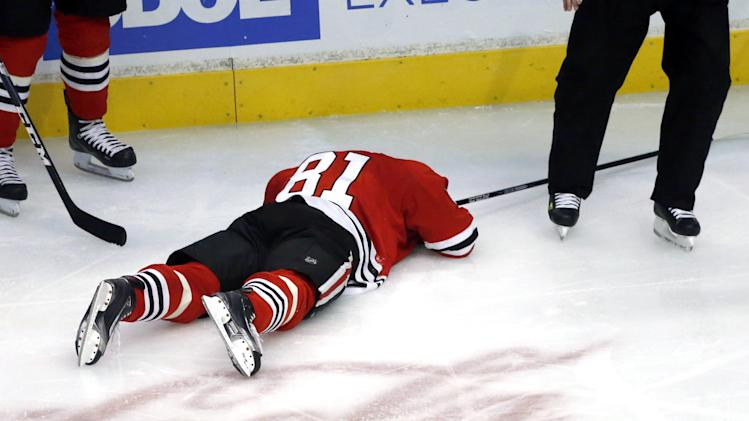 Chicago Blackhawks right wing Marian Hossa, from Slovakia, lays on the ice after being hit in the back of the head by Vancouver Canucks right wing Jannik Hansen, from Denmark, during the third period of an NHL hockey game Tuesday, Feb. 19, 2013 in Chicago. The Blackhawks won 4-3 in a shootout. (AP Photo/Charles Rex Arbogast)