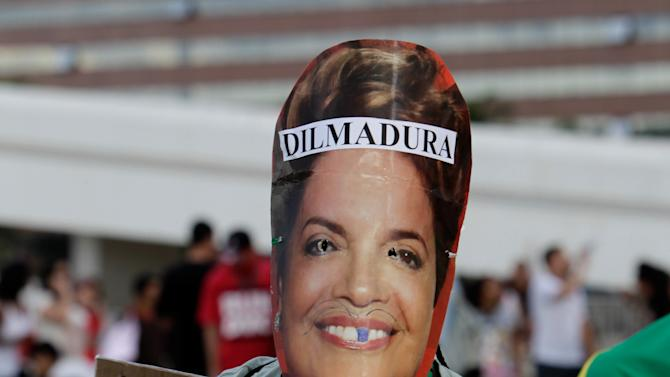 """A demonstrator wearing a mask of Brazil's President Dilma Rousseff holds a protest sign that reads in Portuguese """"No vandalizing, arrest corrupt politicians"""" during a protest against sexism and in defense of women's rights in Brasilia, Brazil, Saturday, June 22, 2013. The sign on Rousseff's head is a play on words that means """"Iron Dilma.""""A career technocrat and trained economist, Rousseff's tough managerial style under Silva earned her the moniker """"the Iron Lady,"""" a name she has said she detests. (AP Photo/Eraldo Peres)"""