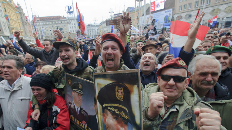 War veterans celebrate during the live broadcast from the International War Crimes Tribunal, on Zagreb's main square, Friday, Nov. 16, 2012. Appeals judges at the Yugoslav war crimes tribunal have overturned the convictions of two Croat generals for crimes against humanity and war crimes committed against Serb civilians in a 1995 military blitz. Ante Gotovina and Mladen Markac, were sentenced to 24 and 18 years respectively in 2011 for crimes, including murder and deportation. Judges ruled both men were part of a criminal conspiracy led by former Croat President Franjo Tudjman to expel Serbs. (AP Photo/Nikola Solic)