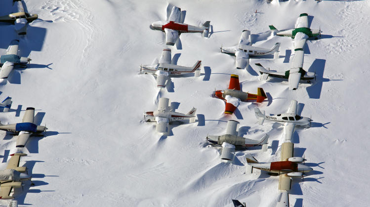 Small planes are snowed in at the closed Bridgeport, Conn., airport  Sunday, Feb. 10, 2013, in the aftermath of a storm that hit Connecticut and much of the New England states. (AP Photo/Craig Ruttle)