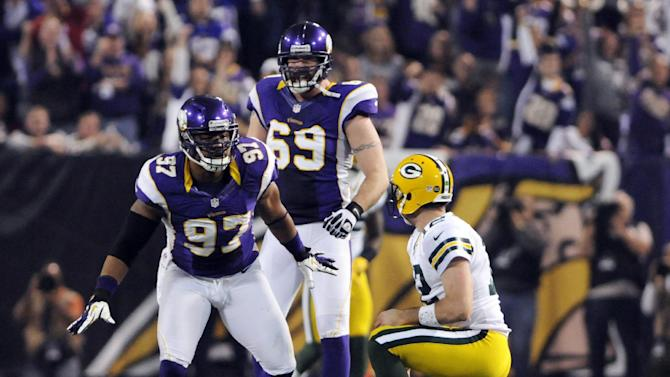 Minnesota Vikings defensive end Everson Griffen (97) reacts with teammate Jared Allen (69) after sacking Green Bay Packers quarterback Aaron Rodgers, right, during the first half of an NFL football game Sunday, Dec. 30, 2012, in Minneapolis. (AP Photo/Jim Mone)