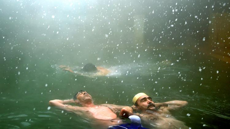 In this Feb. 19, 2014 photo, Iranian men relax in a hot mineral water spring as snow falls lightly, in the northwestern town of Sarein, Iran. The steamy waters emanating from the depths of the earth are rich in sulfur, calcium, lithium and other minerals, and are believed to offer relief to patients suffering from joint pain and some skin diseases. The hot springs, in Sarein, also offer an affordable getaway for Iranians from all walks of life. (AP Photo/Ebrahim Noroozi)