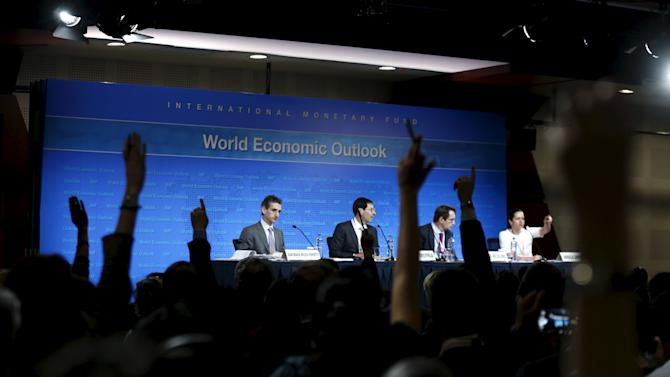 Participants attend the International Monetary Fund's media briefing on the world economic outlook during its annual meeting in Lima