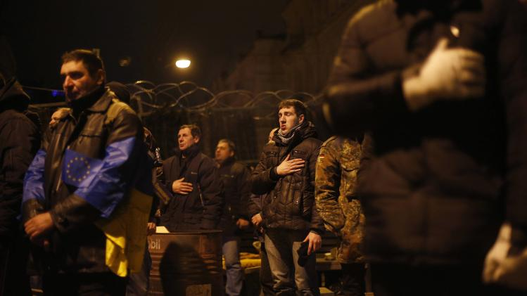 A protester sings the Ukrainian national anthem at a barricade at Independence Square in Kiev