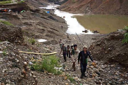 Hand-pickers return from searching for jade through rubble dumped by mining companies at a jade mine in Hpakant township, Kachin State