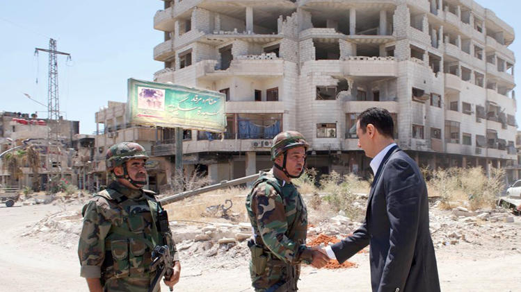 This image posted on the official Facebook page of the Syrian Presidency on Thursday, Aug. 1, 2013 purports to show Syrian President Bashar Assad shaking hands with a solider during Syrian Arab Army day in Darya, Syria. Syrian state-run TV says Assad has visited a tense Damascus suburb to inspect his troops on the occasion of the country's Army Day. The visit on Thursday is Assad's first known public trip outside the capital, his seat of power, since he visited the Baba Amr district in the central city of Homs after troops seized it from rebels in March 2012. Daraya, just south of Damascus, was held by rebels for a long time and it took the army weeks of heavy fighting to regain control earlier this year. (AP Photo/Syrian Presidency via Facebook)