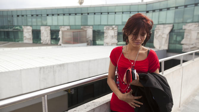 Sam, the Belizean girlfriend of software company founder John McAfee, stands in the La Aurora international airport after McAfee was released from a detention center and brought to the airport in Guatemala City, Wednesday, Dec. 12, 2012. McAfee, who is being deported to the U.S., was detained last week for immigration violations after he sneaked into Guatemala from neighboring Belize, where authorities sought to question him about the murder of his neighbor. (AP Photo/Moises Castillo)