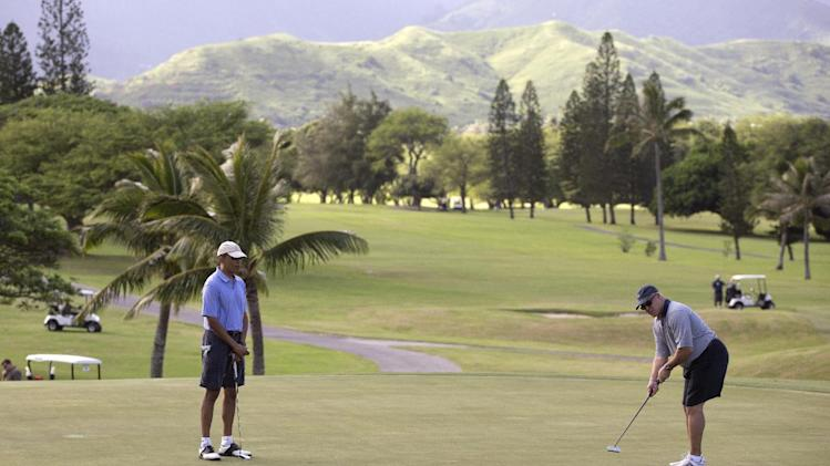 U.S. President Barack Obama, left, watches close friend Eric Whitaker putt on the 18th green at Mid-Pacific County Club in Kailua, Hawaii, Monday, Dec. 23, 2013. The first family is in Hawaii for their annual holiday vacation. (AP Photo/Carolyn Kaster)