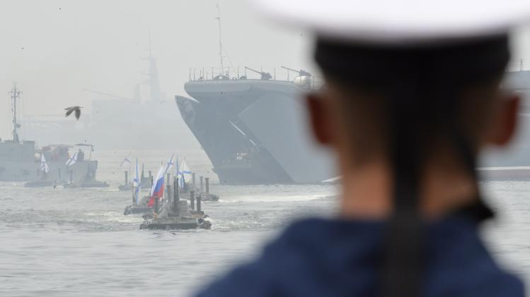 A Russian sailor watches amphibious vehicles move during a naval parade rehearsal in the far eastern port of Vladivostok