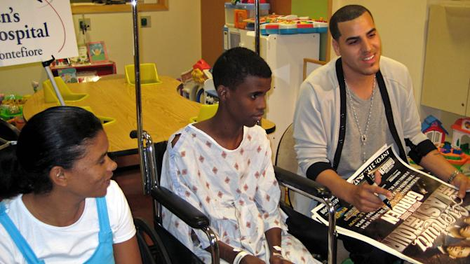Aventura's bass guitarist Max Santos talks with reporters before signing a poster for 15-year-old Dalin Garcia of the Dominican Republic, center, at the Children's Hospital at Montefiore in the in the Bronx borough of New York, Tuesday June 7, 2011.  Dalin's mother, Floridalia de los Santos is seated at left. (AP Photo/Claudia Torrens)