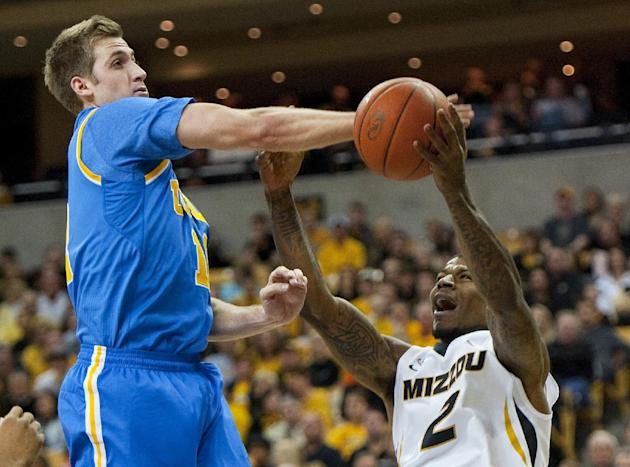 UCLA's David Wear, left, fouls Missouri's Tony Criswell, right, as he tries to shoot during the first half of an NCAA college basketball  game Saturday, Dec. 7, 2013, in Columbia, Mo
