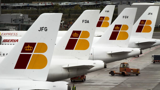 """A man walks besides Iberia jets in a parking zone at Barajas international airport in Madrid, Friday, Nov. 9, 2012. International Airlines Group on Friday warned that its Spanish carrier Iberia was """"in a fight for survival"""" and unveiled a restructuring plan to cut 4,500 jobs as it reported a drop in third-quarter profit. (AP Photo/Daniel Ochoa de Olza)"""