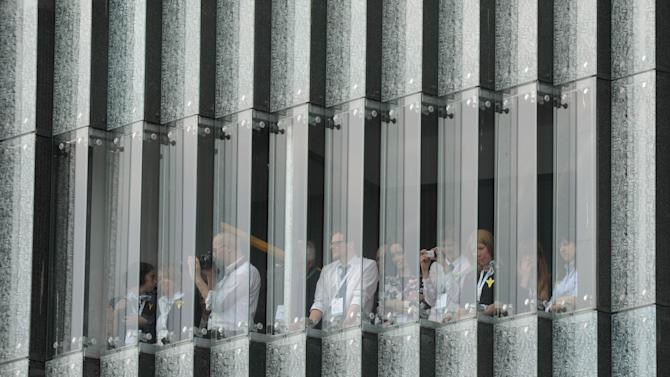 Workers of the Museum of the History of Polish Jews watch from their building ceremonies marking the 70th anniversary of the outbreak of the Warsaw Ghetto Uprising, in Warsaw, Poland, Friday, April 19, 2013. (AP Photo/Alik Keplicz)