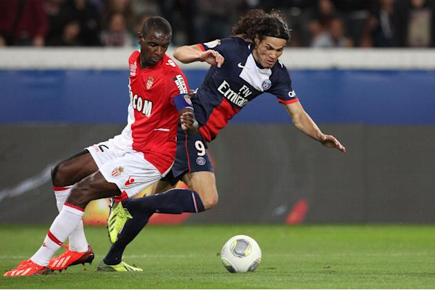 Paris Saint Germain's forward Edinson Cavani from Uruguay, centre,  challenges for the ball with Monaco's defender Eric Abidal, during their French League One soccer match, at the Parc des Princes sta