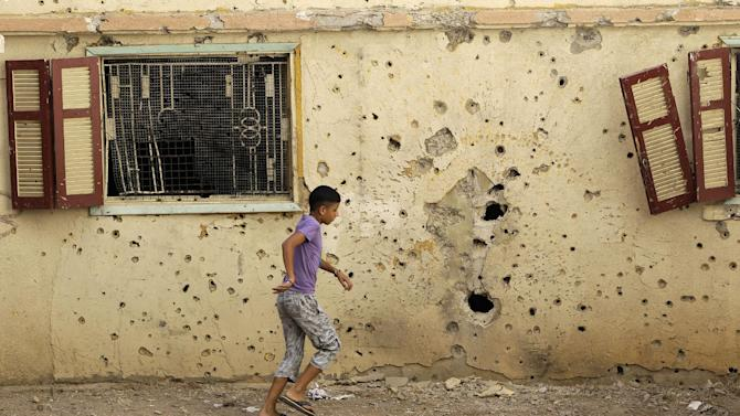A Lebanese boy walks past a house that was hit by rockets on a frontline street where clashes erupted between pro and anti-Syrian regime groups, in the northern city of Tripoli, Lebanon, Thursday Aug. 23, 2012. The latest clashes were between gunmen from the Sunni neighborhood of Bab Tabbaneh and the neighboring Jabal Mohsen, which is mostly populated by followers of the Alawite sect, an offshoot of Shiite Islam. The clashes that began Monday left at least a dozen people dead and dozens more wounded. (AP Photo/Hussein Malla)
