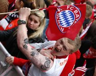 Bayern Munich supporter Florian Holland shows his tattoos while waiting for the Bayern team with the German soccer championship trophy during a reception at Munich's townhall May 11, 2013. German Bundesliga soccer clubs Borussia Dortmund and Bayern Munich will play in the Champions League final at Wembley in London on May 25, 2013. REUTERS/Michaela Rehle/Files (GERMANY - Tags: SPORT SOCCER)