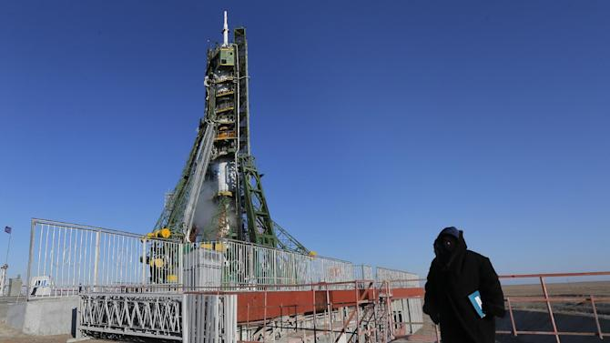 A security guard stands in front of the Soyuz TMA-07M spacecraft shortly before its launch with the International Space Station (ISS) crew at the Russian leased Baikonur cosmodrome, Kazakhstan, Wednesday, Dec. 19, 2012.  (AP Photo/Dmitry Lovetsky, pool)