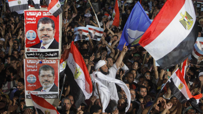 "Supporters of Egypt's Islamist President Mohammed Morsi wave national flags and his posters during a rally in Nasser City, in Cairo, Egypt, Monday, July 1, 2013. Egypt's powerful military warned on Monday it will intervene if the Islamist president doesn't 'meet the people's demands,' giving him and his opponents two days to reach an agreement in what it called a last chance. Hundreds of thousands of protesters massed for a second day calling on Mohammed Morsi to step down. Arabic reads "" Mohammed Morsi for Egyptian presidency. "" (AP Photo/ Amr Nabil)"