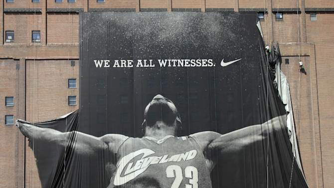 FILE - In this July 11, 2010 file photo, a 10-story banner of former Cleveland Cavaliers NBA basketball star LeBron James is taken down by workers in downtown Cleveland, Ohio. James told Sports Illustrated on Friday, July 11, 2014, he is leaving the Miami Heat to go back to the Cleveland Cavaliers. (AP Photo/Amy Sancetta, File)