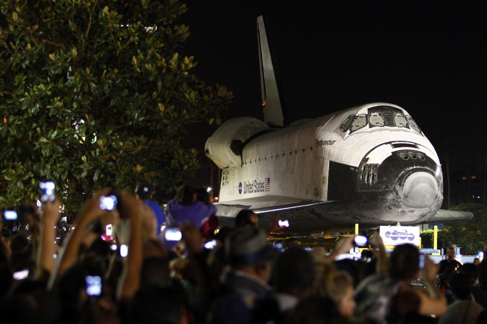 Spectators take pictures as the space shuttle Endeavour makes its way through city streets in Los Angeles, Calif., Saturday, Oct. 13, 2012. Endeavour's 12-mile road trip kicked off shortly before midnight Thursday as it moved from its Los Angeles International Airport hangar en route to the California Science Center. (AP Photo/Patrick T. Fallon)