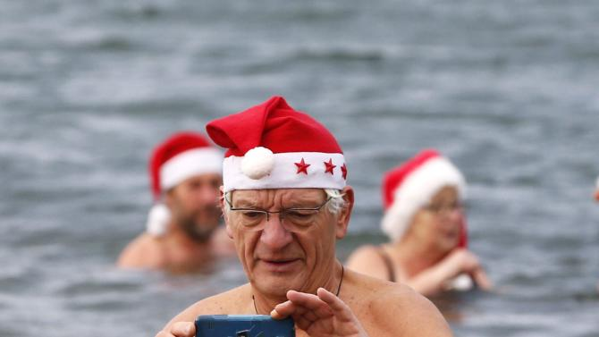 """A member of the ice swimming club """"Berliner Seehunde"""" (Berlin Seals) takes pictures with his mobile phone as he takes a dip in the Orankesee lake in Berlin as part of their traditional Christmas ice swimming session"""