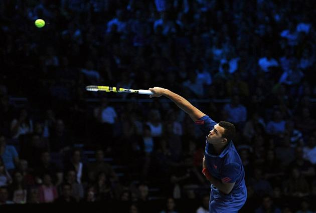 France's Jo-Wilfried Tsonga serves against Serbia's Novak Djokovic during their group A singles match in the round robin stage on the first day of the ATP World Tour Finals tennis tournament in London