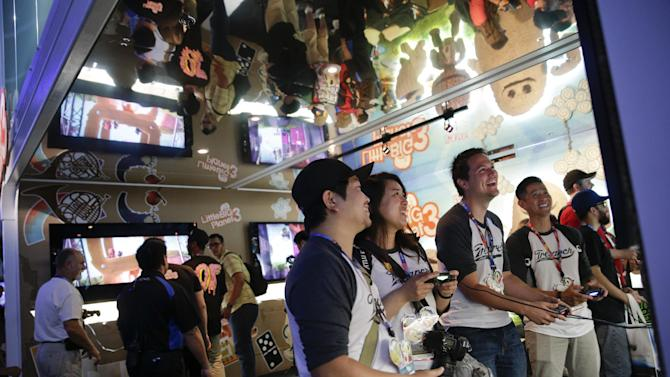 """Show attendees play the """"LittleBigPlanet 3"""" video game at the Sony booth at the Electronic Entertainment Expo on Tuesday, June 10, 2014, in Los Angeles. (AP Photo/Jae C. Hong)"""