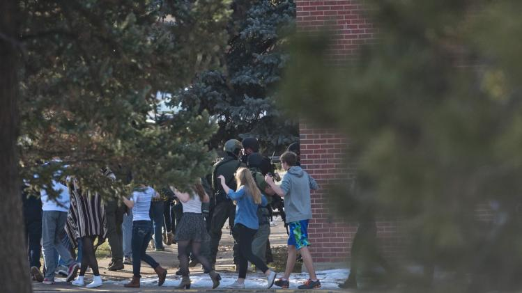 Students walk with their hands raised as they are escorted out of Arapahoe High School, after a student opened fire in the school in Centennial, Colorado