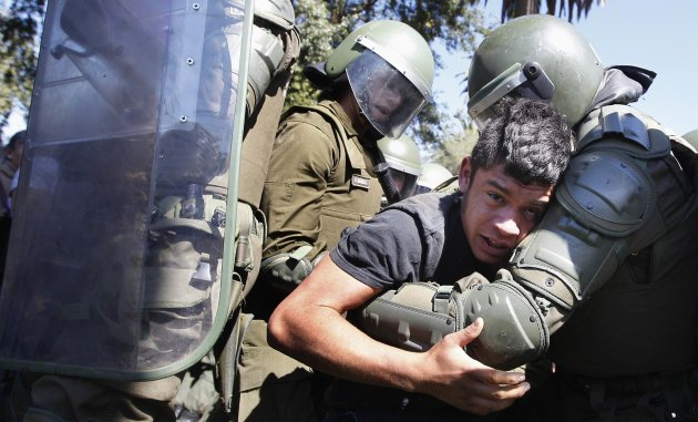 A student is detained by riot police during a rally in Valparaiso