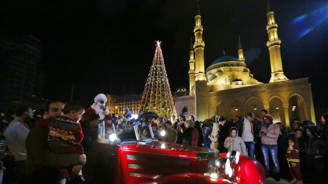 A man dressed as Santa Clause stands in a Red car in a parade during a Christmas tree lighting in downtown Beirut