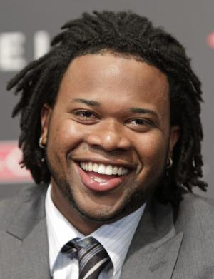 Cincinnati Reds pitcher Johnny Cueto breaks into a smile during a news conference where it was announced he had agreed to a $27 million, four-year contract with the baseball team, Wednesday, Jan. 26, 2011, in Cincinnati. (AP Photo/Al Behrman)