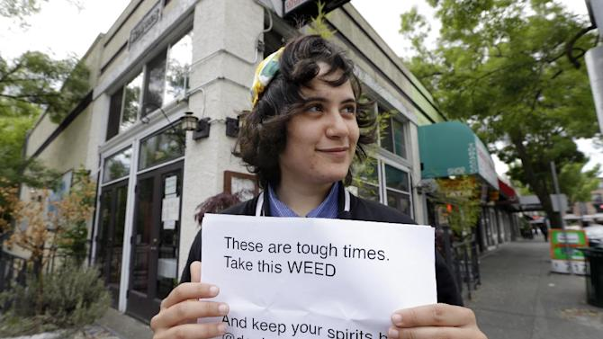 """Yeni Sleidi, known as the """"weed fairy,"""" poses for a photo in Seattle's Capitol Hill neighborhood Wednesday, May 28, 2014, where this past weekend she posted 50 fliers with nuggets of marijuana taped to them. Sleidi, a 23-year-old who works in social media, has been visiting Seattle from New York where last year she did a similar posting, albeit anonymously. (AP Photo/Elaine Thompson)"""