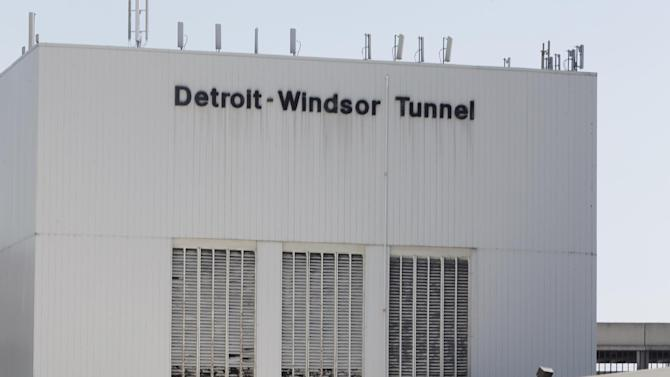 Vehicles block the entrance as authorities investigate a bomb threat at the Detroit Windsor Tunnel Thursday, July 12, 2012. The tunnel was closed to traffic after the threat was called in on the Canadian side, tunnel chief executive Neal Belitsky told The Associated Press. The call was made some time after 12:30 p.m. to the duty free shop on a plaza on the tunnel's Windsor side, tunnel executive vice president Carolyn Brown said. The underwater tunnel stretches about a mile beneath the Detroit River, which is one of North America's busiest trade crossings.(AP Photo/Paul Sancya)