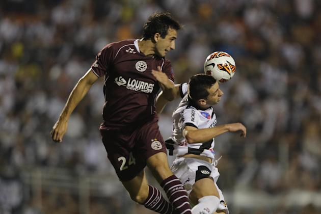 Elias of Brazil's Ponte Preta, right, and Carlos Izquierdoz of Argentina's Lanus fight for the ball during the first leg match of Copa Sudamericana final in Sao Paulo, Brazil, Wednesday, Dec.