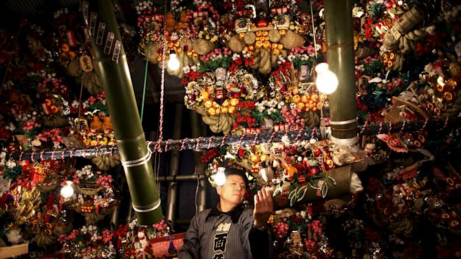 "A vendor arranges rakes, or ""kumade"", decorated with imitation gold coins and other objects to sell during the Tori-no-Ichi fair at Ohtori shrine in downtown Tokyo, Japan"