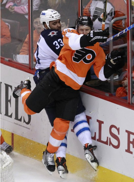 Flyers center Schenn checks Jets defenseman Byfuglien into the boards during the first period of their NHL ice hockey game in Philadelphia, Pennsylvania