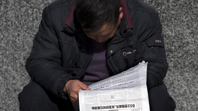 A Chinese man reads a newspaper which reports that U.S., Japan and South Korea sent flights through China's newly declared maritime air defense zone, in Beijing, China Friday, Nov. 29, 2013. China said it sent warplanes into the air defense zone days after the U.S., South Korea and Japan all sent flights through the airspace in defiance of rules Beijing says it has imposed in the East China Sea. (AP Photo/Andy Wong)
