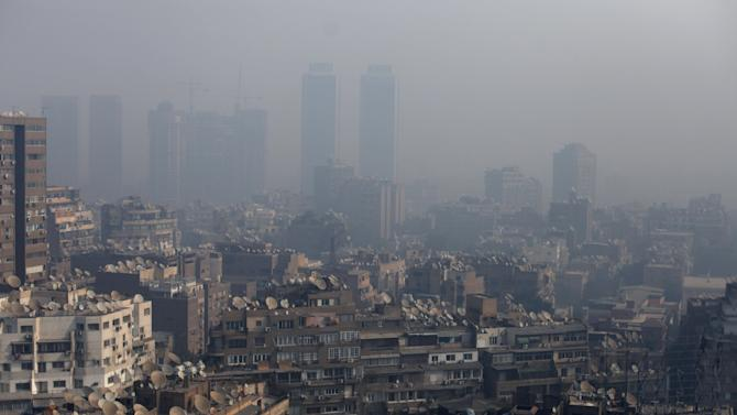 Residential buildings are obscured by heavy air pollution in Cairo, Egypt Wednesday, Jan. 16, 2013. Cairo has air pollution levels from 10 to 100 times higher than the World Health Organization standards. High vehicle fuel emissions, polluting urban industries, and a hot and dry desert climate are causing havoc to the occupants of this city. (AP Photo/Khalil Hamra)