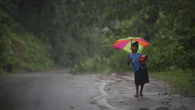 A student walks back home after attending school as it rains at Reba Maheswar village, 56 kilometers (35 miles) east of Gauhati, India, Friday, July 3, 2015. (AP Photo/ Anupam Nath)