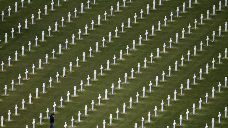 An aerial view shows a man walking among tombstones as he visits the World War II Normandy American Cemetery and Memorial at Colleville sur Mer, situated above Omaha Beach