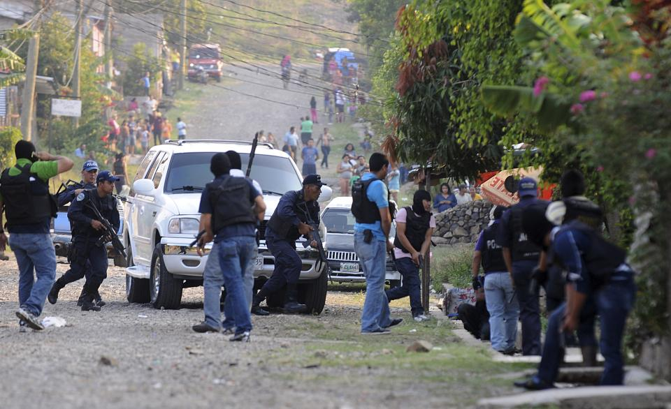 In this April 7, 2013 photo, police react during a shootout that ended in two suspects killed and one officer injured as police carry out an offensive against gang members in Tegucigalpa, Honduras. The officers had surrounded a house where two gangsters had holed up after a chase with police. (AP Photo/Fernando Antonio)