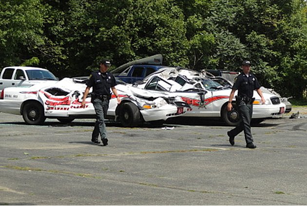 Sheriff officers walk past crushed cruisers at the Orleans County Sheriff's Department in Newport, Vt., Thursday, Aug. 2, 2012. Authorities say 34-year old Vermont farmer Roger Pion, angry over a rece