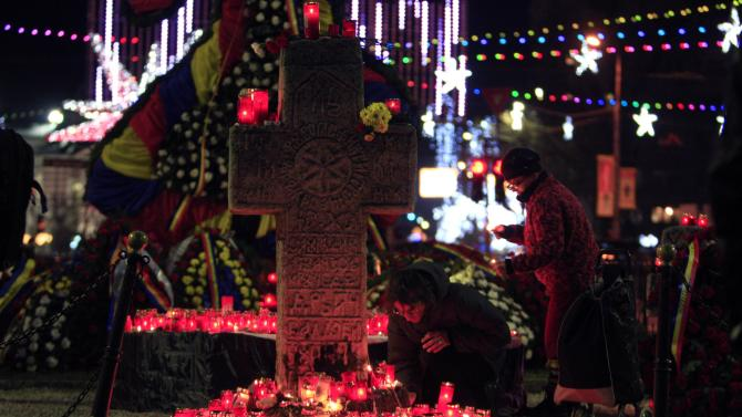 Two women light candles around a cross during the 25th anniversary of the country's 1989 revolution in central Bucharest
